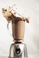 Chocolate Protein Shake Splashing from a Blender