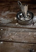 Measuring spoons on a floured wooden surface