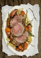 Sliced beef shoulder fillet on a bed of vegetables