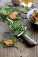 Cutlery tied with carrot stalks and decorated with a place c
