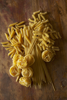 Various types of pasta on a wooden surface 22199074917| 写真素材・ストックフォト・画像・イラスト素材|アマナイメージズ