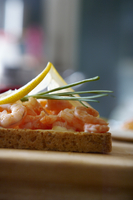 A slice of toast topped with prawns, lemons and chives
