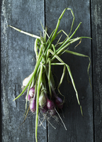 A bunch of spring onions on a wooden surface (seen from abov