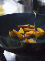 Honey being added to pieces of pumpkin in a pan