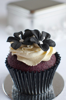 A red velvet cupcake with butter cream and sugar flowers