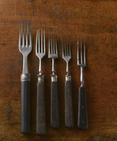Five old forks on a wooden surface