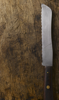 A bread knife on a wooden surface