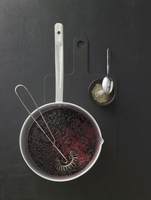 Cornflour being stirred into elderberry sauce