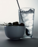 A cocktail with ice cubes and a bowl of olives