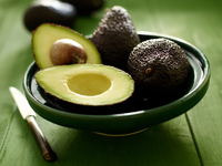 Avocados, whole and halved, in a green bowl