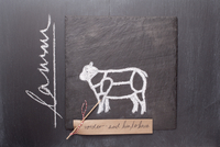 A sketch of a lamb, a label with writing on a chalkboard