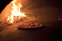 Pizza Cooking in a Brick Oven 22199075611| 写真素材・ストックフォト・画像・イラスト素材|アマナイメージズ