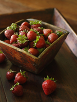 Fresh Strawberries in and Around a Wooden Bowl