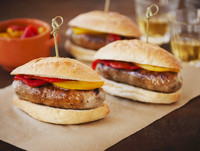 Sausage Sandwiches with Red and Yellow Peppers on Paper; Wit