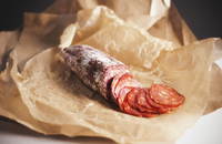 Partially Sliced Salami on Paper
