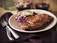 Grass Fed Rib-Eye Steak Served with Cabbage Salad and Red Wi