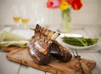 Rack of Lamb on a Cutting Board with Asparagus and Wine in t