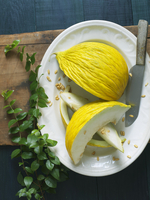Casaba Melon Cut into Wedges on a Platter with Knife and See