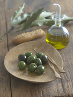 Green Olives with Olive Oil on a Wooden Dish; Carafe of Oliv