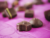 Chocolate Candies on Pink; One with a Bite Taken Out