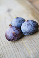 Three fresh figs on a wooden surface