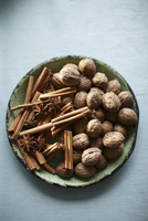 Cinnamon stick, star anise and walnuts on a rustic plate