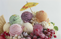 Various scoops of ice cream, frozen berries, cream and a coc