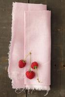 Three raspberries on a pink linen cloth