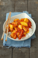 Sweet and sour chicken on a bed of rice noodles (Asia)