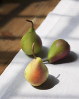 Three pears on a white linen table cloth