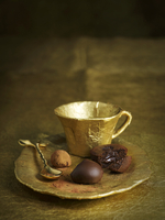 A gold coffee cup with filled chocolates on the saucer