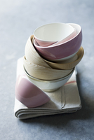 A stack of cereal bowls on a tea towel