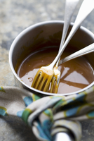 Caramel sauce in a saucepan with forks