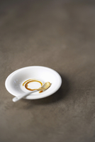 A coffee cup ring on a saucer and a used coffee spoon