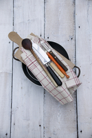 Cutlery, kitchen utensils, a tea towel and a chopping board, on top of a pan