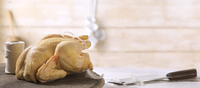 A whole fresh chicken on a worktop