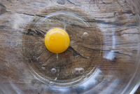 A raw egg in a glass bowl (view from above)