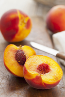 Peaches, whole and halved, on a wooden board with a knife 22199078489  写真素材・ストックフォト・画像・イラスト素材 アマナイメージズ
