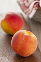 Two whole peaches on a wooden board 22199078490  写真素材・ストックフォト・画像・イラスト素材 アマナイメージズ