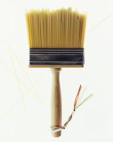 A paintbrush with bristles made of spaghetti and little ribbons in the Italian colours
