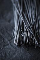 Squid ink spaghetti on black slate (close-up)