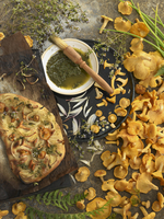 A still life featuring focaccia, chanterelles and thyme pesto