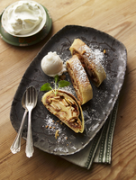 Apple and hazelnut strudel with icing sugar, vanilla ice cream and cream