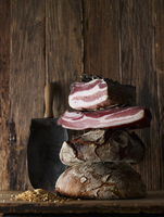 Rustic bread, cured ham and cereal grains on a wooden surface 22199078684| 写真素材・ストックフォト・画像・イラスト素材|アマナイメージズ
