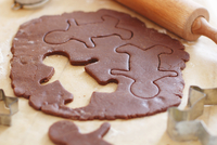 Gingerbread dough with one biscuit cut out and removed