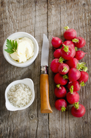 Radishes with salt, butter and a knife on a wooden surface