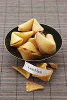 Fortune cookies in a bowl on a bamboo mat