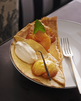 Pancake topped with caramelised apples and vanilla ice cream