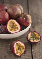Several passion fruit, whole and cut in half 22199079166| 写真素材・ストックフォト・画像・イラスト素材|アマナイメージズ