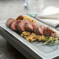 Sliced Grilled Tenderloin of Beef and Bacon Blue Cheese Pastina Risotto with Quenelle of Tomato Jam and Burgundy Jus